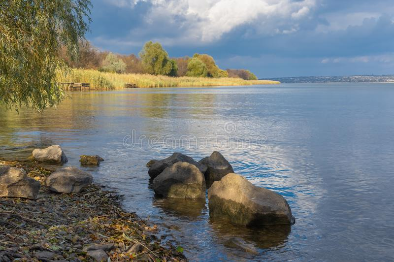 Landscape with rocky riverside on Dnipro river at fall season. Autumnal landscape with rocky riverside on Dnipro river at fall season stock images