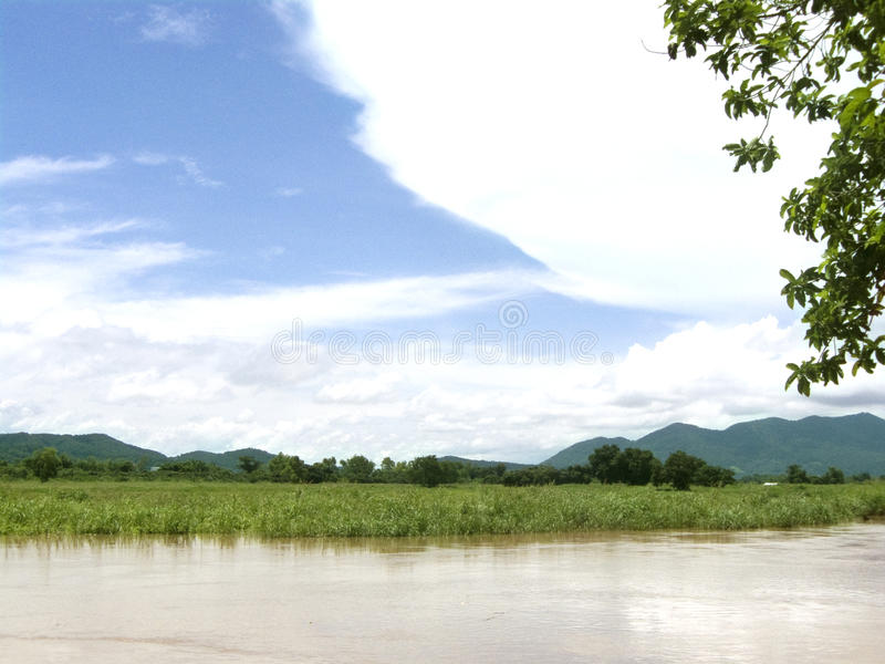 Landscape of rural at the river side. Of natural, can see flooding of corn field at the side of river and green mountain behind the field and blue sky with stock image