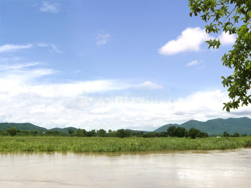 Rural at the river side landscape. Landscape of rural at the river side of natural, can see flooding of corn field at the side of river and green mountain behind royalty free stock photography
