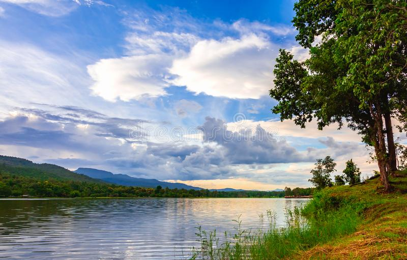 Landscape scene of lake, tree and mountain in cloudy sunset sky royalty free stock photography