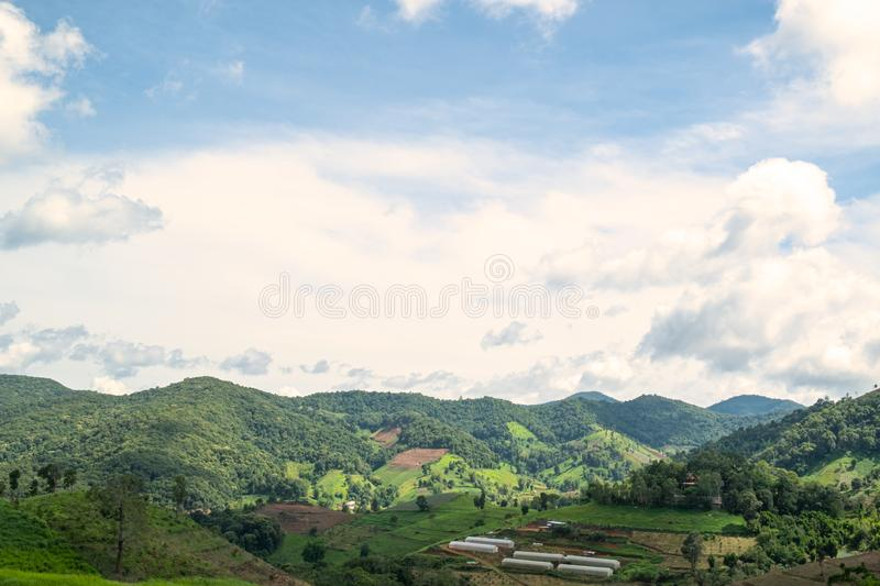 Landscape scenery view of greenery mountain with beautiful sky. There are vegetable plots and white plant nursery tents in the valley, agriculture, background royalty free stock photos