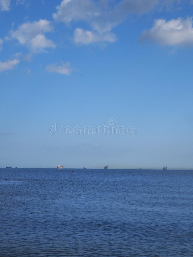 Blue sea horizon line with ships stock photography