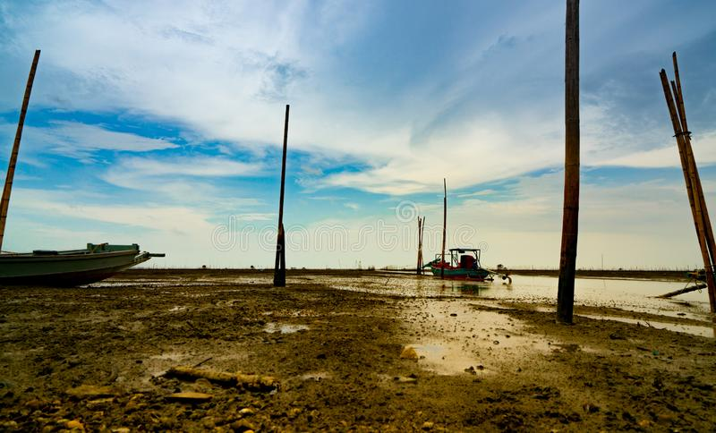 Landscape of sea at tide and blue sky and clouds with fisherman`s boat. Sea mud beach when the water lower. Fishing boat parked royalty free stock image