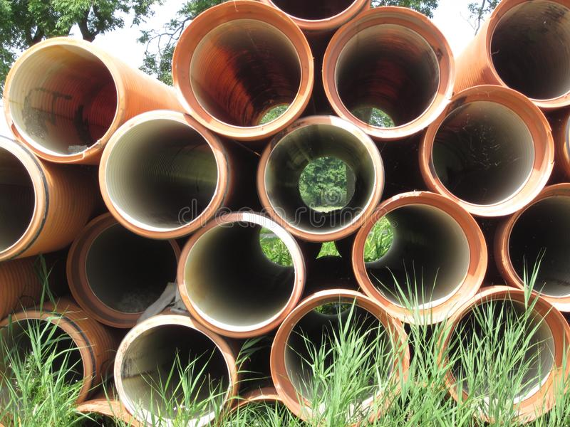 Landscape seen through orange colored sewer pipes stock photography