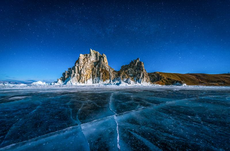 Landscape of Shamanka rock and star on sky with natural breaking ice in frozen water on Lake Baikal, Siberia, Russia stock photo