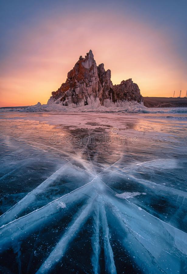 Landscape of Shamanka rock at sunrise with natural breaking ice in frozen water on Lake Baikal, Siberia, Russia.  stock photos