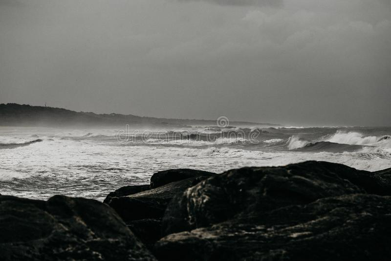 Landscape shot of a rough body of water with waves splashing onto the rocky shore stock images