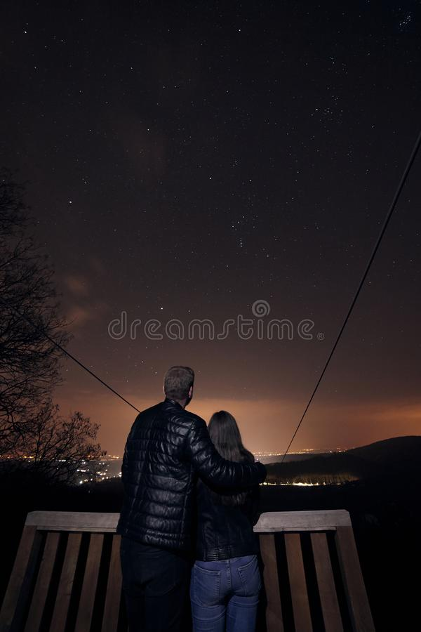 Landscape shot, young couple starring in stars in night time, far in nature wilderness. Astrophotography royalty free stock images