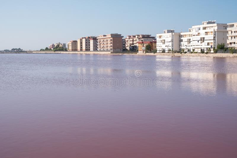 Landscape showing pink salt flats at Margherita Di Savoia in Puglia, Italy. Water is pink crustaceans that live in it. Pink salt flats at Margherita Di Savoia royalty free stock image