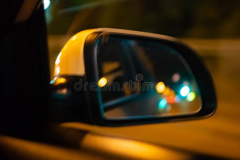 Landscape in the sideview mirror of a car , on the night road. In the side mirror of the car is reflected the lights of the night stock photography