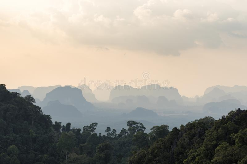 Silhouettes tropical hazy mountains and the green jungle trees in the foreground royalty free stock photos