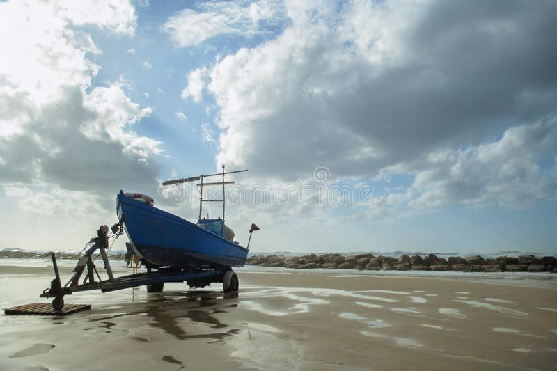Landscape of Sironit beach, Natanya, Israel. Old blue fishing boat on three-wheeled cart on sand of Sironit beach, Netnya, Israel. Backgound of sea and sky with royalty free stock images