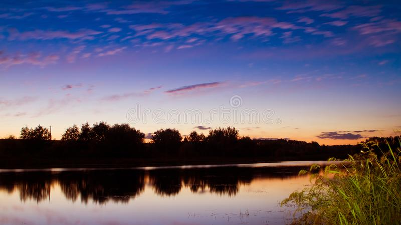 Landscape of a small countryside pond in early still and warm summer night with beautiful dark blue sky and beautiul little clouds stock image