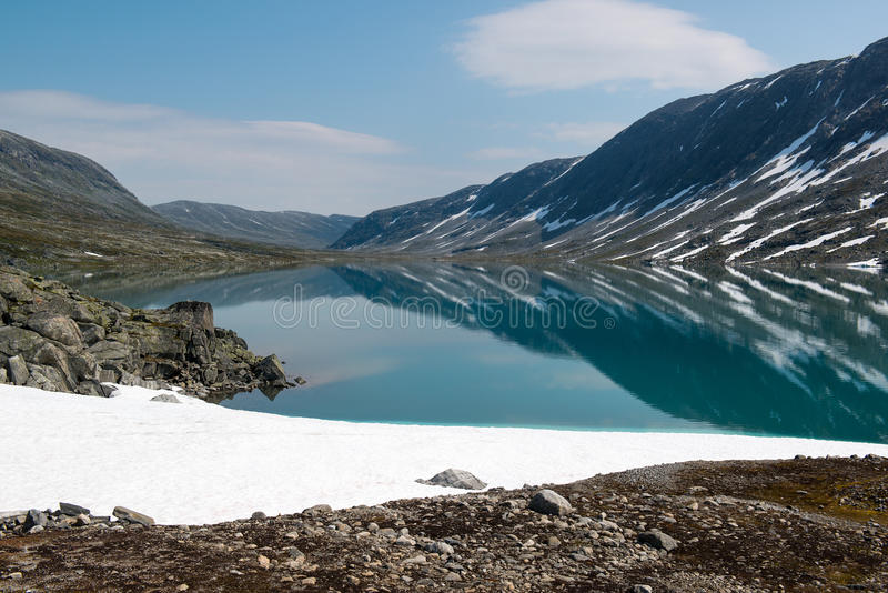 Landscape with snow, mountain lake and reflection, Norway stock photo