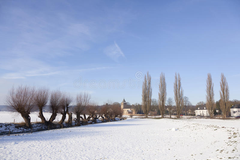 Landscape with snow near old church in Oosterbeek on sunny winter day. Landscape near Arnhem with snow near old church in Oosterbeek on sunny winter day in the royalty free stock image