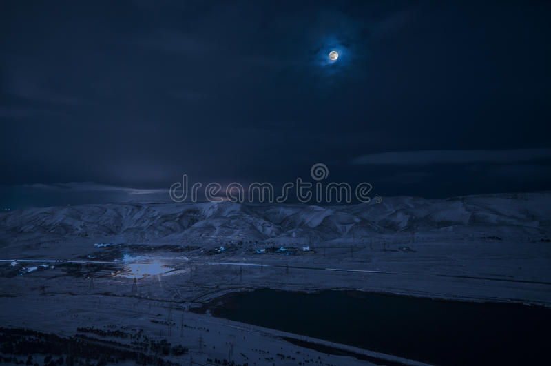 Landscape of snowy mountains and lake with full moon above. The moon and clouds on sky. Baku, Azerbaijan, Xojasan Lake stock image