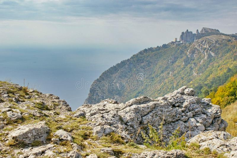 View of rocky mountainside on black sea with a peak on top. View of the rocky mountainside with a stone peak on top of the Ai-Petri mountain against of blue sea royalty free stock photography