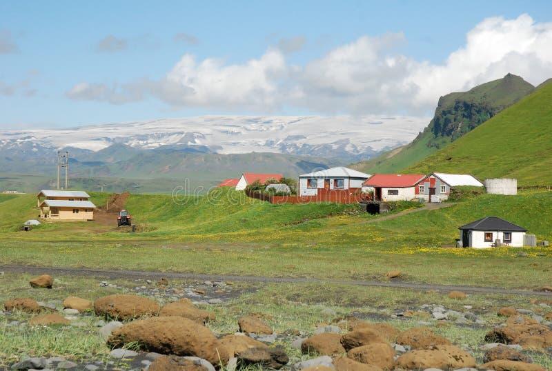 Iceland landscape south coast - with glacier-grassland. Glacier with snow - green grassland - houses , Iceland landscape south coast royalty free stock image