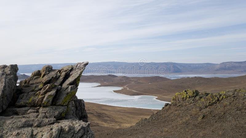 Landscape of the southern part of Olkhon island in Siberia. Mountainous terrain, steppes and frozen lake Baikal royalty free stock image