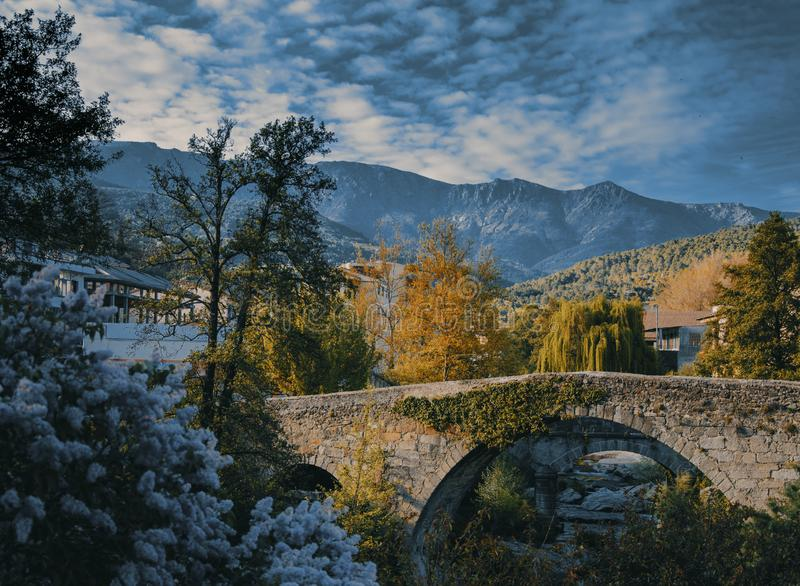Bucolic landscape of old village including stone bridge royalty free stock image