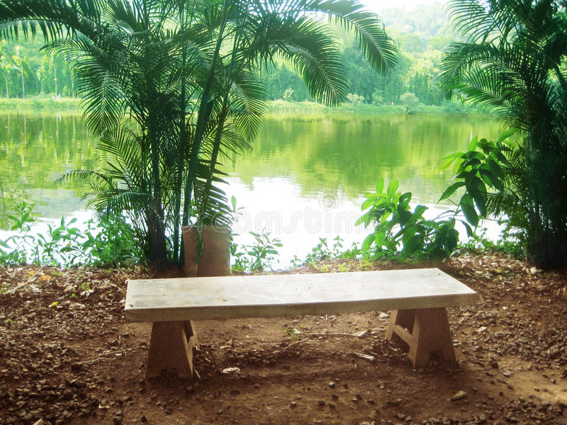 Landscape of a stone chair of relaxing corner. In front of the natural pond in the forest, Nakhon Nayok Province, Thailand royalty free stock photo