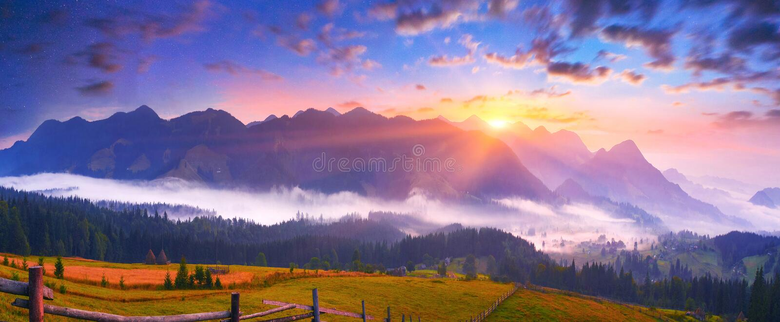 Landscape of summer mountains with rising sun. Panoramic landscape with mountain mist at sunrise stock photography