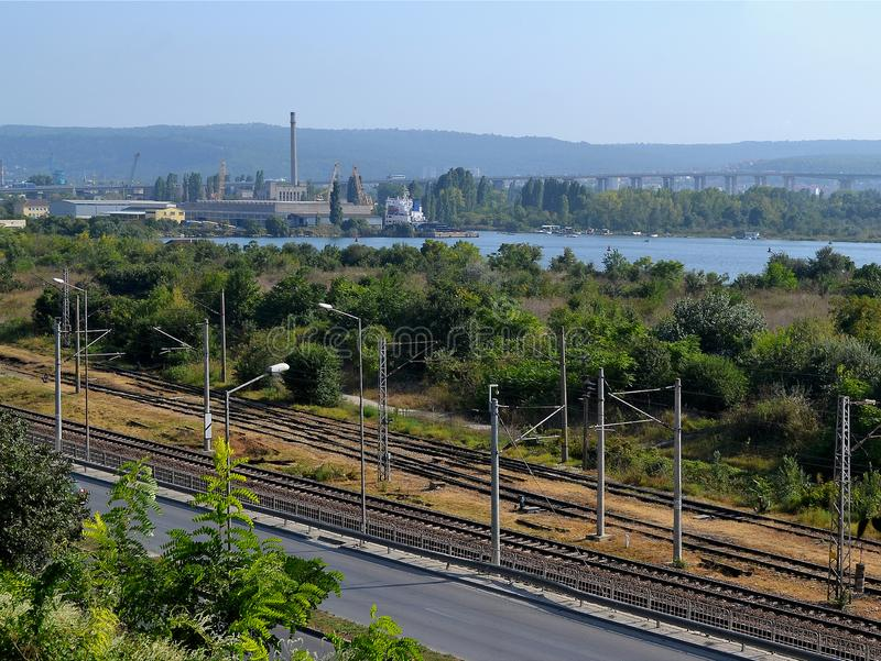 Landscape on summer sunny day: highway running along the railway, industrial building, cranes and green wood on a lake shore royalty free stock images