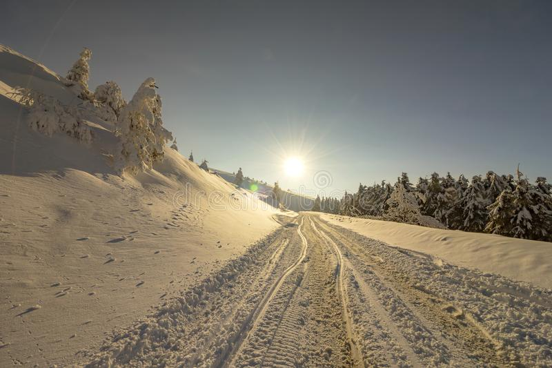 Winter road in the mountain. Landscape with sun, snow and car tracks on the road in the winter in the mountain. The concept of winter travel by car royalty free stock photography