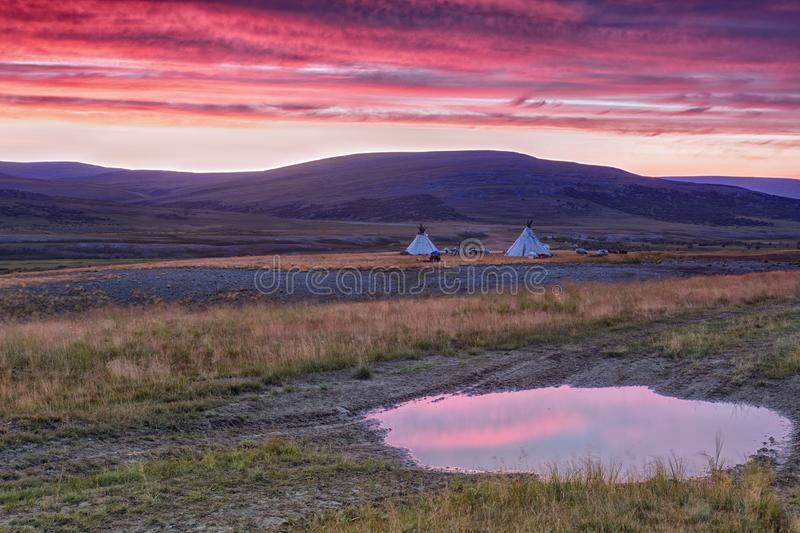 Landscape at sunrise with sky reflected in a large puddle. Dwellings of nomads and mountains, Russia, Yamal stock photography