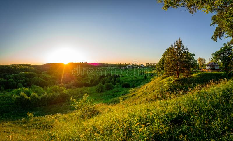 Landscape at sunset in Central Russia. The landscape at sunset is rich in colors. Illuminated by Golden sunlight, fields, meadows, trees, hills and village stock image