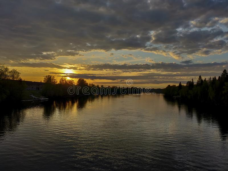 Landscape of sunset in a cloud covered sky with silhouette of forst trees and reflection in river water royalty free stock photography