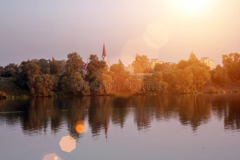 Landscape sunset with European town and lake. Autumn landscape with yellow and green trees and river royalty free stock image