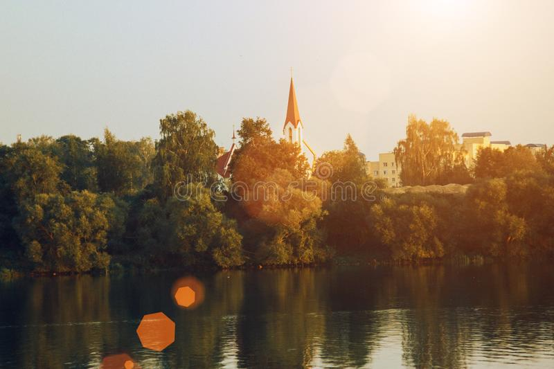 Landscape sunset with European town and lake. Autumn landscape with yellow and green trees and river royalty free stock images