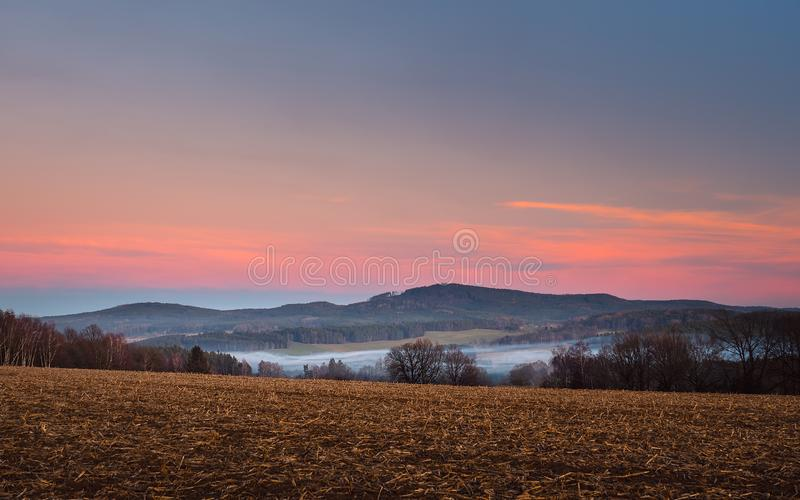 Landscape at sunset, in the foreground field and trees, in the valley white fog, in the background forest and mountains royalty free stock images