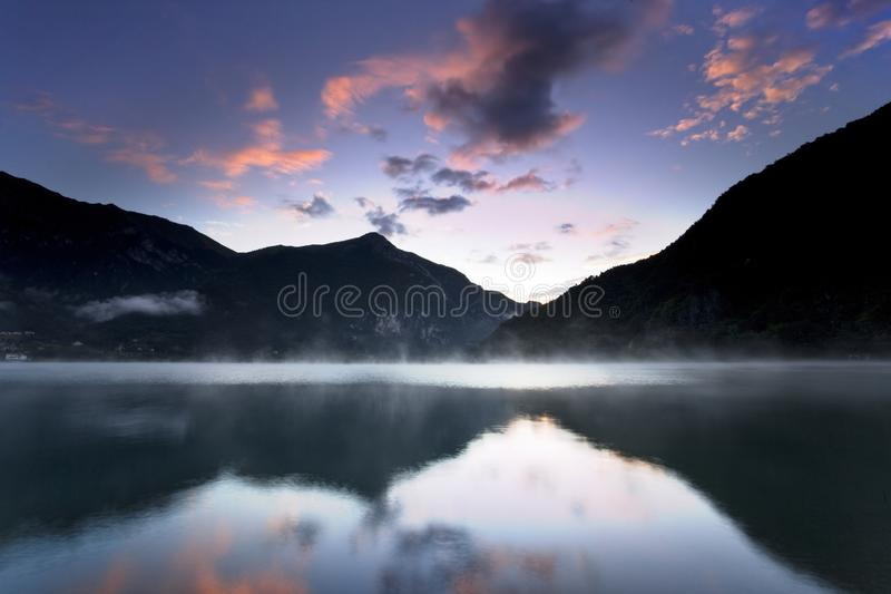 Landscape with sunset lake reflections in autumn, location Alps, Italy, Europe colorful autumn trees reflecting in lake. Landscape with sunset lake reflections stock images