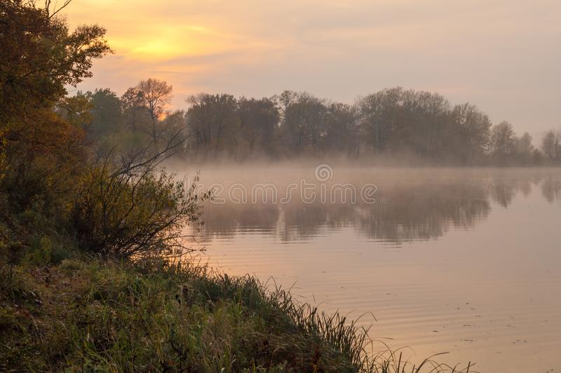Landscape. Sunset over the lake, fall trees reflected in water. Fog, mist, haze, smoke, brume, toman royalty free stock photo