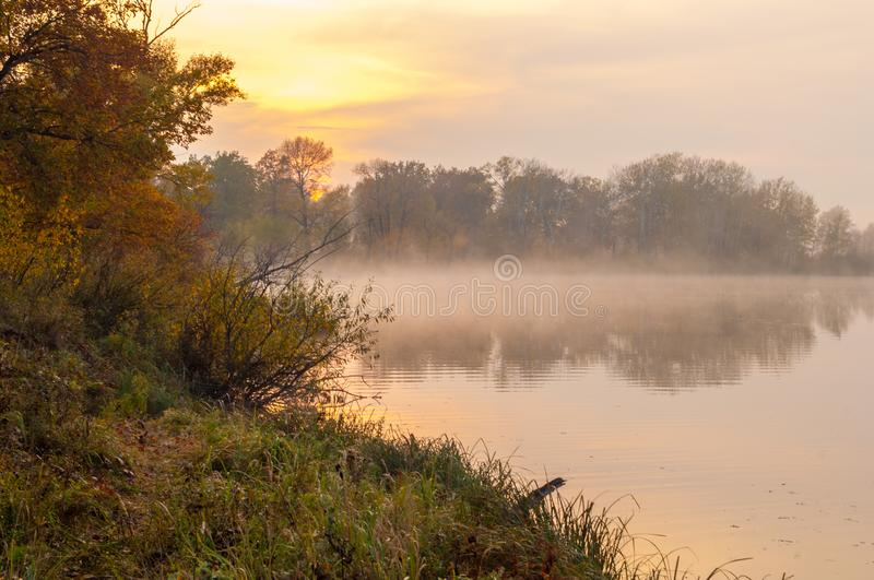 Landscape. Sunset over the lake, fall trees reflected in water. Fog, mist, haze, smoke, brume, toman royalty free stock photos