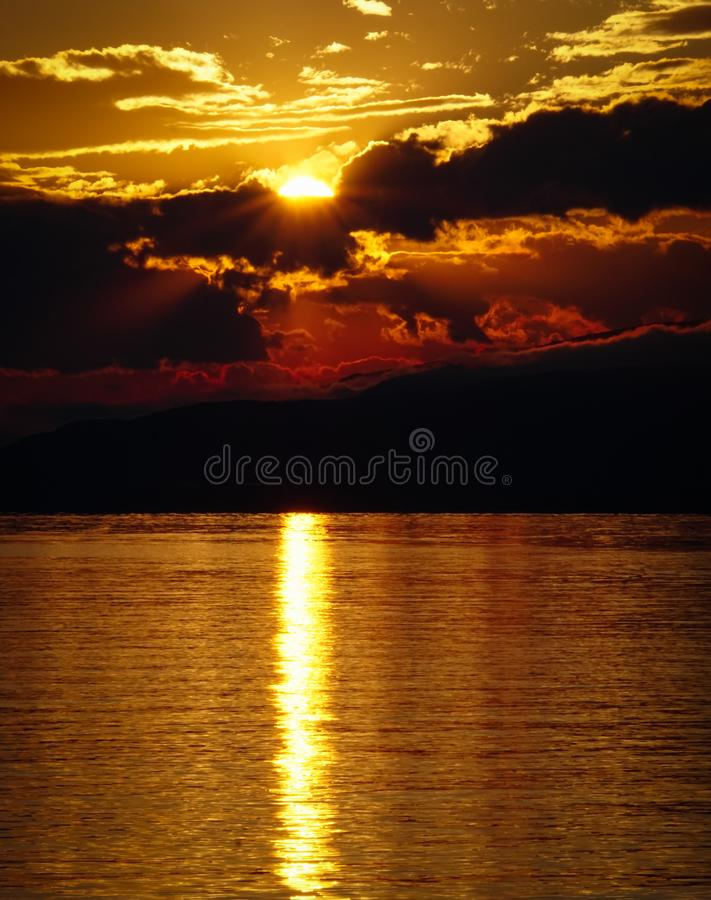 Landscape of sunset over the lake and mountains. Cloudy sky. Iznik, Bursa, Turkey.  stock photos