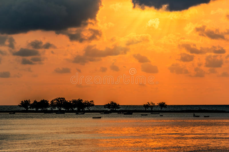 Landscape sunset, the sea waves, fishing boat in Thailand.  stock photos