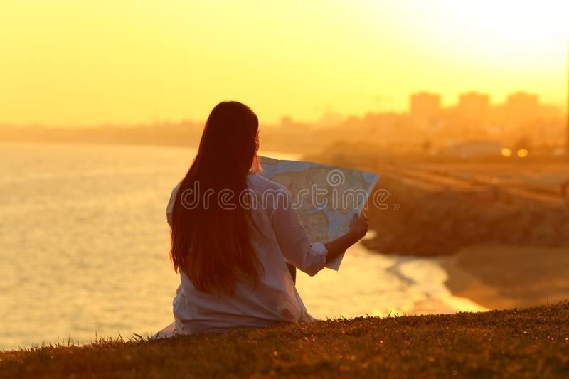 Landscape with a tourist reading a map at sunset royalty free stock photos