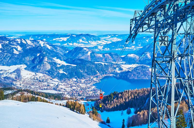 The landscape with tower of Zwolferhorn cableway, St Gilden, Salzkammergut, Austria. The colorful vintage gondolas of Zwolferhorn cable car run along the snowy royalty free stock photography
