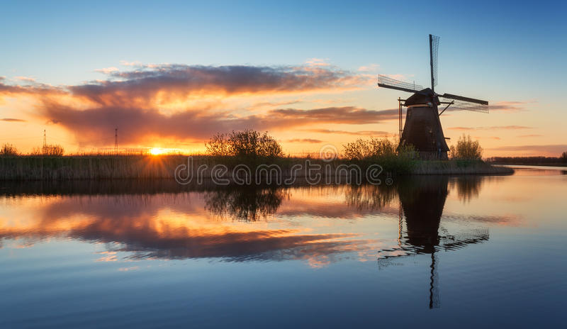 Landscape with traditional dutch windmills at colorful sunrise royalty free stock photography