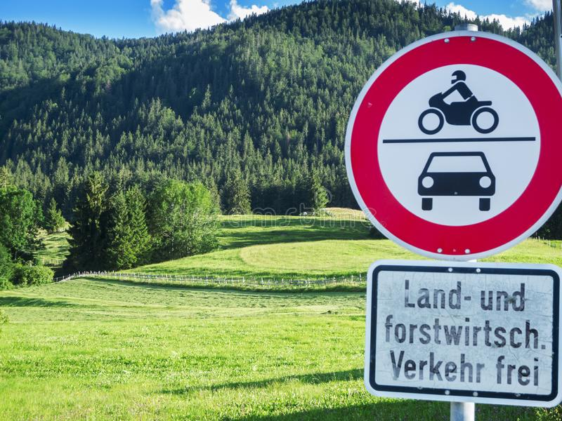 Landscape with forest and pasture and traffic signs. Bavarian mountain landscape with cattle pasture and driving prohibition signs for motor vehicles, except royalty free stock photo