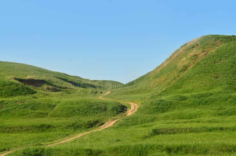 Landscape with a trampled path, passing through a wonderful green mountainous terrain. Photo of beautiful landscaped relief space royalty free stock photography