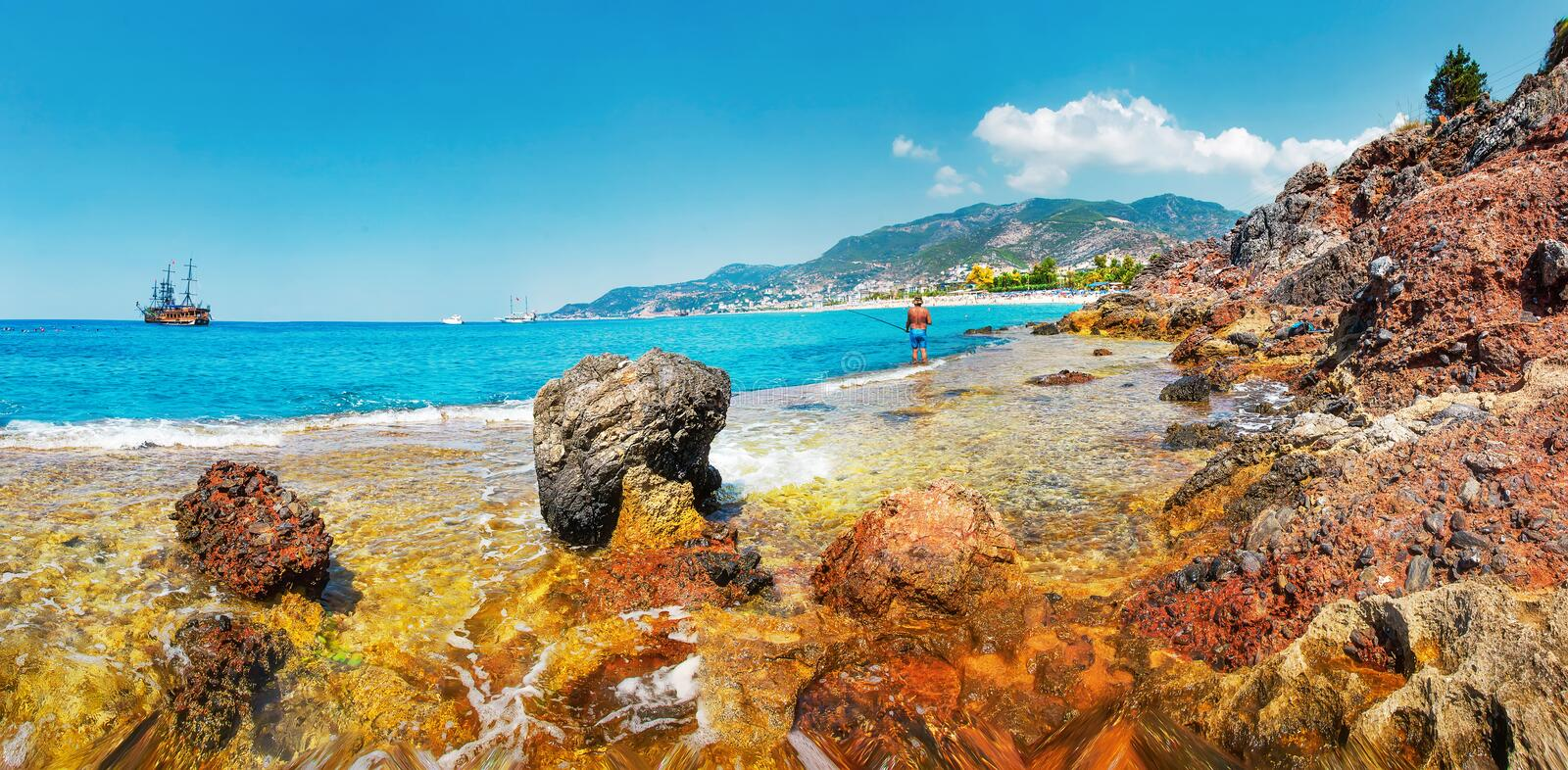 Landscape of tropical rocky beach on sunny summer day. The fisherman catches fish in the warm sea waters from the shore stock image