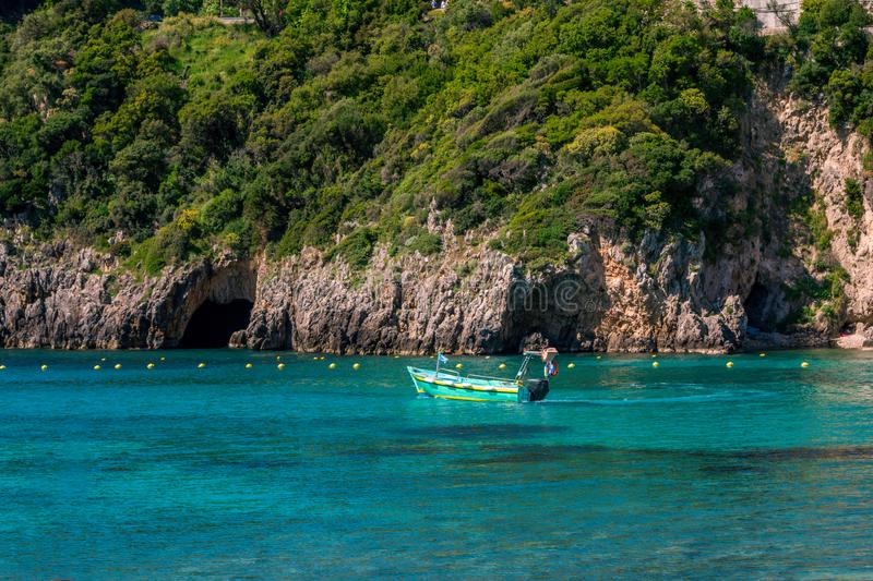 Landscape with turquoise calm sea water, mountain caves and touristic boat. Landscape with turquoise calm sea water, mountain with rocky hillside covered with royalty free stock image