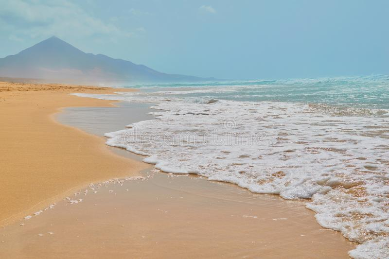 Landscape of turquoise water beach and stone mountain in Cofete, Fuerteventura. Landscape of turquoise water beach and stone mountain with golden sand and sea royalty free stock images