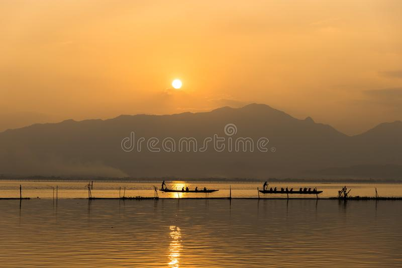Landscape view - boatman paddle boat in the lagoon lake.Kwan phayao in evenign time at phayao thailand royalty free stock image