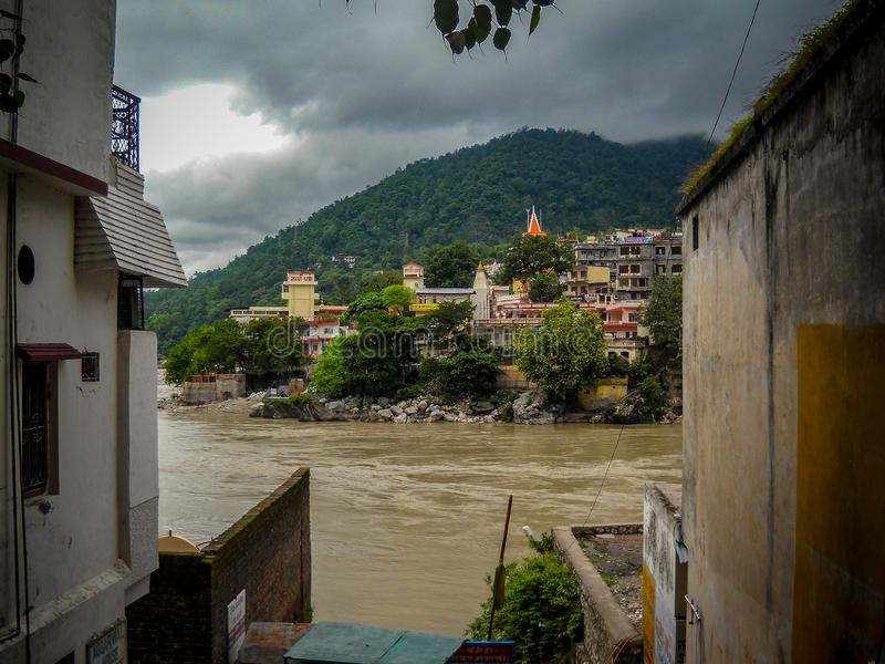 Landscape view of Ganga river having mountains & clouds at rishikesh India royalty free stock image
