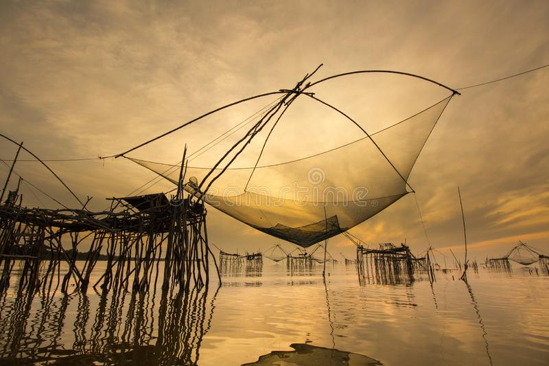 Landscape Amazing giant fish lift net in Phatthalung,Thailand. Landscape view  giant fish lift net with sunrise and golden sky reflection in canal during travel royalty free stock image